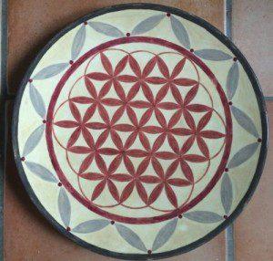 beiger Keramikteller mit roter Blume des Lebens