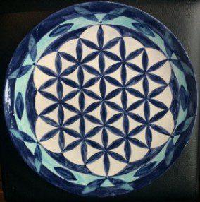 weißer Keramikteller mit blauer Blume des Lebens